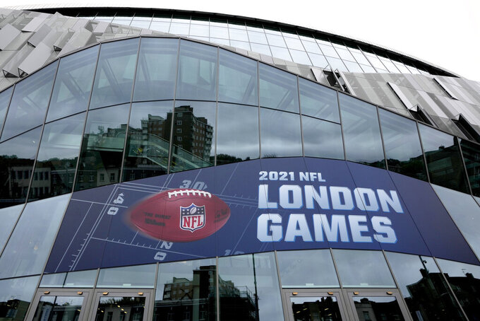 Buildings are reflected in the glass of the stadium as advertising promotes the NFL games to be played at the Tottenham Hotspur Stadium in London, Thursday, Oct. 7, 2021. After a one-year hiatus due to the pandemic, the NFL returns to London on Sunday when the Atlanta Falcons play the New York Jets at Premier League club Tottenham's $1.6 billion facility (AP Photo/Kirsty Wigglesworth)
