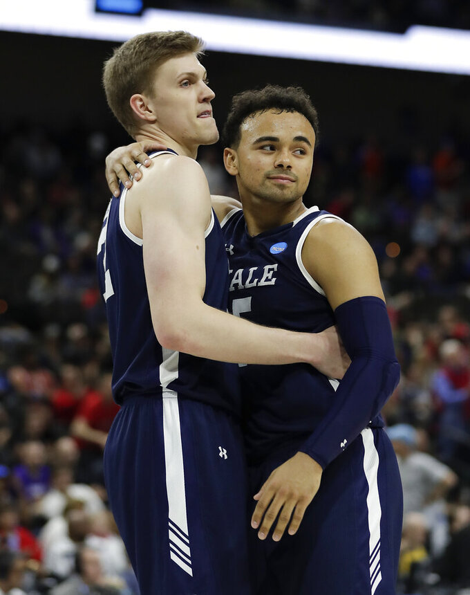 Yale 's Blake Reynolds, left, and Azar Swain console each other after losing 79-74 to LSU in a first round men's college basketball game in the NCAA Tournament, in Jacksonville, Fla. Thursday, March 21, 2019. (AP Photo/John Raoux)