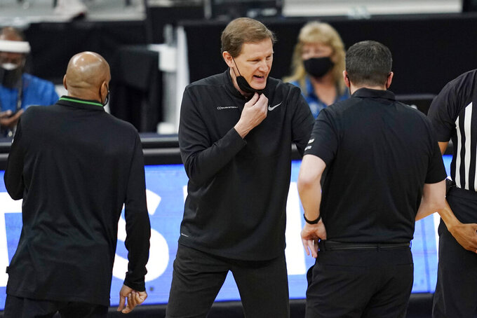Oregon head coach Dana Altman, center, speaks with assistant coaches during the first half of an NCAA college basketball game in the quarterfinal round of the Pac-12 men's tournament Thursday, March 11, 2021, in Las Vegas. (AP Photo/John Locher)
