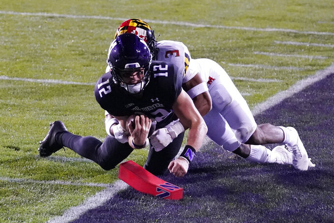Northwestern quarterback Peyton Ramsey (12) scores a touchdown as Maryland defensive back Nick Cross tackles during the first half of an NCAA college football game in Evanston, Ill., Saturday, Oct. 24, 2020. (AP Photo/Nam Y. Huh)