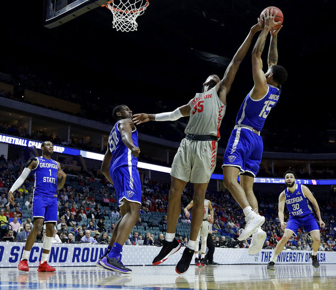 Houston's Fabian White Jr. (35) and Georgia State's D'Marcus Simonds (15) battle for a rebound during the first half of a first round men's college basketball game in the NCAA Tournament Friday, March 22, 2019, in Tulsa, Okla. (AP Photo/Charlie Riedel)