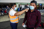 Passengers have their temperature measured before boarding a humanitarian flight to Canada at the La Aurora international airport in Guatemala City, Thursday, Sept. 17, 2020. Authorities are preparing for the reopening of the airport on Friday as part of the gradual reopening of the country's borders by allowing national flights and some duly authorized international flights. (AP Photo/Moises Castillo)