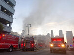 Firefighters respond to an explosion in downtown Los Angeles that has injured multiple firefighters and caused a fire that spread to several buildings, Saturday, May 16, 2020, in Los Angeles. (AP Photo/Stefanie Dazio)