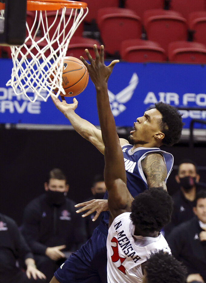 Nevada guard Desmond Cambridge Jr. (4) shoots as San Diego State forward Nathan Mensah (31) defends during the first half of an NCAA college basketball game in the semifinal round of the Mountain West Conference men's tournament Friday, March 12, 2021, in Las Vegas. (AP Photo/Isaac Brekken)