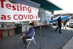 Ricardo Sojuel waits for a coronavirus swab as workers start to dismantle a mobile COVID-19 testing unit, Thursday, July 2, 2020, in Lawrence, Mass. (AP Photo/Elise Amendola)