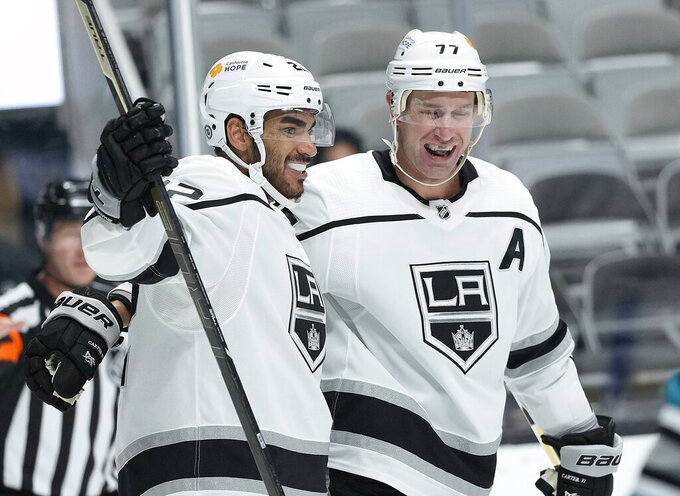 Los Angeles Kings left wing Andreas Athanasiou (22) celebrates with center Jeff Carter (77) after scoring a gaol against the San Jose Sharks during the second period of an NHL hockey game Saturday, April 10, 2021, in San Jose, Calif. (AP Photo/Tony Avelar)