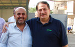 In this 2009 photo from left, Khodeir Majid  and Iraq senior producer Ahmad Sami stand at the AP office in Baghdad. Majid, who covered Iraq's numerous conflicts as a video producer and cameraman for the Associated Press over 17 years has died at the age of 64. Relatives said the cause of his death on Friday morning was complications due to the coronavirus.   (AP Photo/Ahmad Sami)