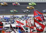 FILE - In this Oct. 7, 2007, file photo, a Confederate flag flies in the infield as cars come out of Turn 1 during a NASCAR auto race at Talladega Superspeedway in Talladega, Ala. NASCAR banned the Confederate flag from its races and venues Wednesday, June 10, 2020, formally severing itself from what for many is a symbol of slavery and racism.  (AP Photo/Rob Carr, File)