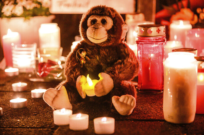This Wednesday, Jan. 1, 2020, file photo, a toy ape is placed between candles at the entrance of the Zoo in Krefeld, Germany. Authorities said rescuers found a gorilla and a female orangutan still alive amid the charred remains of the primate house after the fire on the new year morning. Vets were able to euthanize the orangutan but struggled to do so with the gorilla. After getting permission from a senior officer, a 34-year-old policeman killed the gorilla with shots from his submachine gun. ( Alexander Forstreuter/dpa via AP)