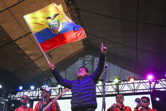 Andres Arauz, presidential candidate of the Alianza Union por la Esperanza, UNES, party waves an Ecuador national flag at his campaign headquarters in Quito, Ecuador, after the closing of the polls for a runoff presidential election Sunday, April 11, 2021. Ecuadorians voted Sunday to choose between Arauz, an economist protégé of former President Rafael Correa, and former banker Guillermo Lasso, of Creating Opportunities party, or CREO. (AP Photo/Dolores Ochoa)
