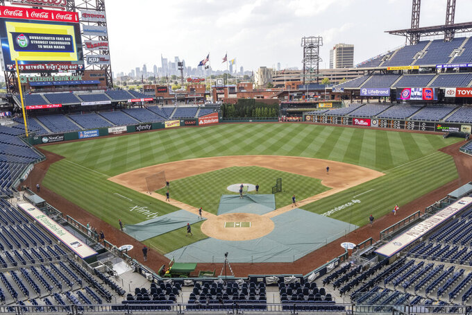 Grounds crew workers clear the field of batting practice equipment after the baseball game between the Philadelphia Phillies and Washington Nationals was suspended due to COVID-19, Wednesday, July 28, 2021, in Philadelphia. (AP Photo/Laurence Kesterson)