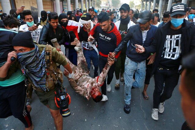 A soldier badly wounded during clashes with anti-government protesters is carried  by demonstrators to a hospital during the ongoing protests in Rasheed Street, Baghdad, Iraq, Tuesday, Nov. 26, 2019. (AP Photo/Khalid Mohammed)