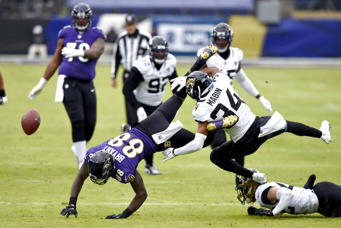Jacksonville Jaguars cornerback Greg Mabin (34) and Baltimore Ravens wide receiver Dez Bryant (88) collide on a pass attempt from Ravens quarterback Lamar Jackson, not visible, during the first half of an NFL football game, Sunday, Dec. 20, 2020, in Baltimore. (AP Photo/Gail Burton)