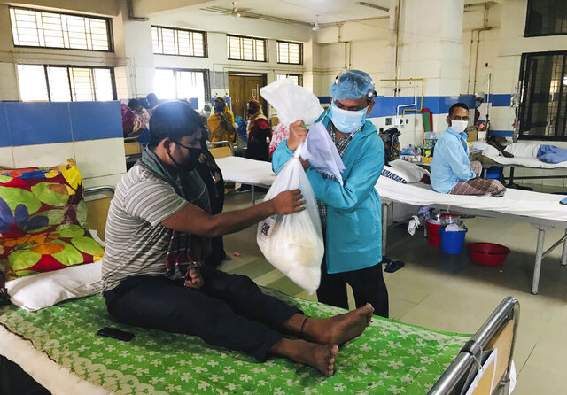 A volunteer of Mission Save Bangladesh distributes food packages at a Cancer hospital in Dhaka, Bangladesh, Thursday, Aug. 20, 2020. With only 20,000 takas ($236) in hand, three friends took up the challenge to channel resources from the generous haves to the desperate have-nots when Bangladeshi authorities prepared to enforce a nationwide lockdown in late March. The first response came from Bangladeshi cricket star Shakib Al Hasan who donated 2 million takas ($24,000). With that, they began distributing food packs in the impoverished neighborhoods in Dhaka. Eventually, they succeeded in bringing about 120 organizations and business houses under one umbrella for their aid campaign, Mission Save Bangladesh. (AP Photo/Al-emrun Garjon)