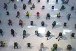 People practice social distancing as they sit on chairs spread apart in a waiting area for take-away food orders at a shopping mall in hopes of preventing the spread of the coronavirus in Bangkok, Thailand, Tuesday, March 24, 2020. (AP Photo/Sakchai Lalit)