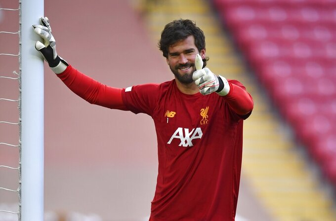 Liverpool's goalkeeper Alisson gestures as he warms-up before the English Premier League soccer match between Liverpool and Chelsea at Anfield stadium in Liverpool, England, Wednesday, July 22, 2020. (Paul Ellis, Pool via AP)