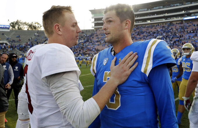 Stanford quarterback K.J. Costello, left, talks to UCLA quarterback Wilton Speight after Stanford's 49-42 win during an NCAA college football game Saturday, Nov. 24, 2018, in Pasadena, Calif. (AP Photo/Marcio Jose Sanchez)