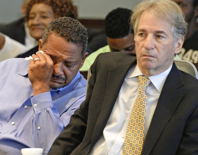 FILE - In this Aug. 31, 2016, file photo, Darryl Howard wipes away tears as he and his lawyer, Barry Scheck, co-director of the based Innocence Project, listen as Judge Orlando Hudson threw out Howard's double-murder conviction after reviewing new DNA evidence, in Durham, N.C. Scheck was the lawyer who introduced DNA science to jurors as he attacked police methods of evidence collection to undermine the prosecution's forensic evidence case. He and fellow O.J. Simpson lawyer Peter Neufeld co-founded The Innocence Project that uses DNA evidence to exonerate wrongly convicted prisoners. The project has helped overturn hundreds of convictions. (Chuck Liddy/The News & Observer via AP, File)