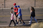 Fans walk along a service road in an effort to see Los Angeles Angels players during a spring training baseball practice, Tuesday, Feb. 23, 2021, in Tempe, Ariz. (AP Photo/Matt York)