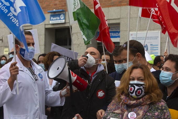 Health workers backed by trade unions protest outside the Hospital Clinico San Carlos in Madrid, Spain, Thursday, Feb. 11, 2021. The workers are calling for better working conditions during the coronavirus pandemic while defending the Spanish national heath service. (AP Photo/Paul White)