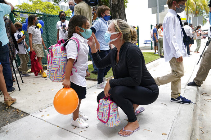 Carol Basilio, right, greets her daughter Giovanna, 4, left, outside of iPrep Academy on the first day of school, Monday, Aug. 23, 2021, in Miami. Public schools in Miami-Dade County have a strict mask mandate to guard against coronavirus infections. A Florida judge ruled Wednesday, Sept. 8, that the state cannot enforce a ban on public schools mandating the use of masks to guard against the coronavirus, while an appeals court sorts out whether the ban is ultimately legal. (AP Photo/Lynne Sladky)
