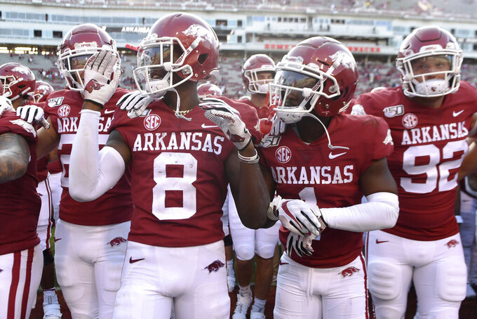 Arkansas' Mike Woods (8) and De'Vion Warren (1) celebrate after the team's 20-13 win over Portland State in an NCAA college football game Saturday, Aug. 31, 2019 in Fayetteville, Ark. (AP Photo/Michael Woods)