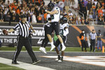 Hawaii running back/wide receiver Calvin Turner Jr., center left, celebrates his touchdown with tight end Caleb Phillips (85) and wide receiver Jared Smart (23) during the first half of an NCAA college football game against Oregon State Saturday, Sept. 11, 2021, in Corvallis, Ore. (AP Photo/Amanda Loman)