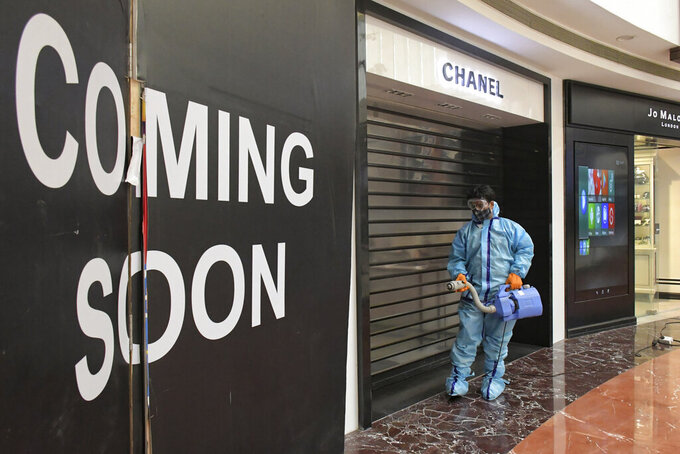 A man sanitizes the premises of a shopping mall before reopening after being closed since April as part of measures to curb the spread of coronavirus in New Delhi, India, Sunday, June 6, 2021. Businesses in two of India's largest cities are reopening as part of a phased easing of lockdown measures in several states now that the number of new coronavirus infections in the country is on a steady decline. (AP Photo/Ishant Chauhan)