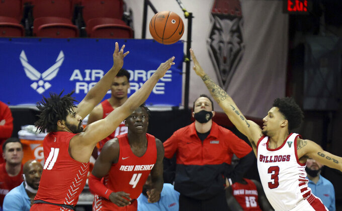 New Mexico guard Jeremiah Francis (11) shoots as Fresno State guard Isaiah Hill (3) defends during the second half of an NCAA college basketball game in the first round of the Mountain West Conference men's tournament Wednesday, March 10, 2021, in Las Vegas. (AP Photo/Isaac Brekken)