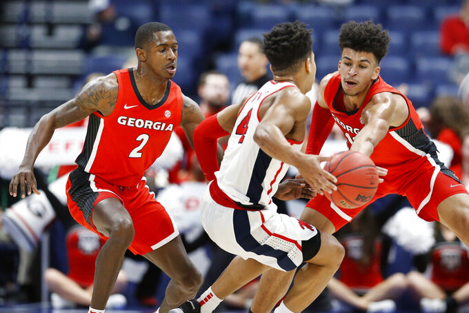 Georgia's Jordan Harris (2) and Toumani Camara, right, block the path of Mississippi's Breein Tyree (4) in the first half of an NCAA college basketball game in the Southeastern Conference Tournament Wednesday, March 11, 2020, in Nashville, Tenn. (AP Photo/Mark Humphrey)
