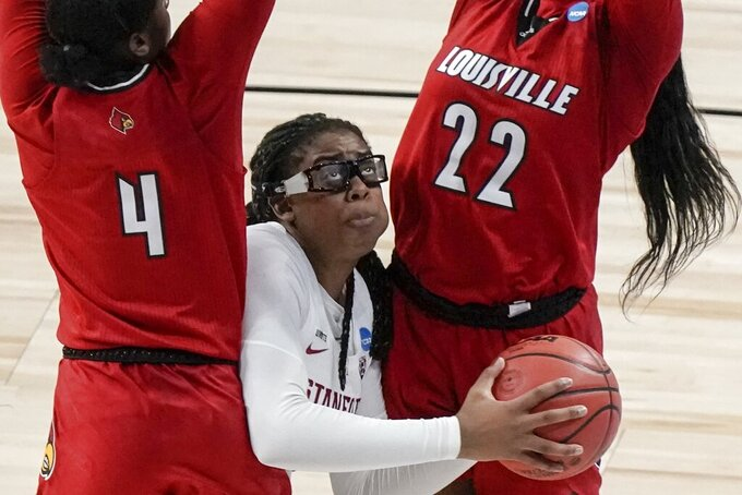 Stanford's Francesca Belibi looks to shoot between Louisville's Elizabeth Balogun and Elizabeth Dixon during the first half of an NCAA college basketball game in the Elite Eight round of the Women's NCAA tournament Tuesday, March 30, 2021, at the Alamodome in San Antonio. (AP Photo/Morry Gash)