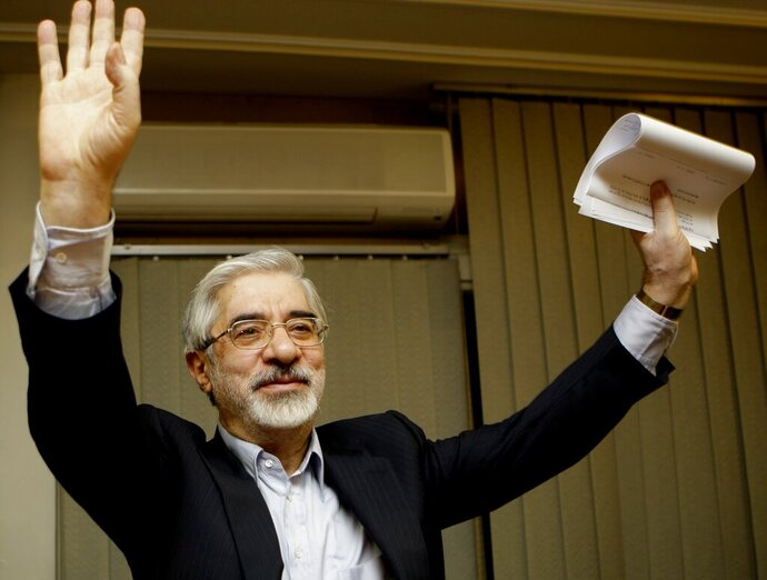 FILE - This Friday, June 12, 2009, file photo, shows Iranian reformist presidential candidate Mir Hossein Mousavi waving to the media during a late night press conference after polls closed in Tehran.  A website long associated with detained opposition leader Mir Hossein Mousavi has quoted him as comparing a crackdown on protesters under Iran's supreme leader to another carried out under the country's ousted shah. The comments published Saturday, Nov. 30, 2019, represent some of the harshest yet attributed to Mousavi, a 77-year-old politician whose disputed election loss in 2009 led to widespread protests before being put down by security forces. (AP Photo/Kamran Jebreili)