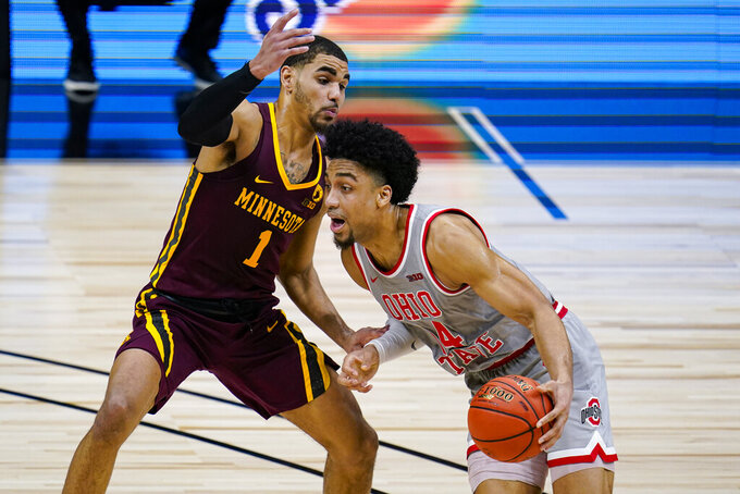 Ohio State guard Duane Washington Jr. (4) drives on Minnesota guard Tre' Williams (1) in the second half of an NCAA college basketball game at the Big Ten Conference tournament in Indianapolis, Thursday, March 11, 2021. Ohio State defeated Minnesota 79-75. (AP Photo/Michael Conroy)