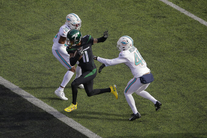 New York Jets wide receiver Robby Anderson (11) splits the defense between Miami Dolphins defensive back Nik Needham (40) and free safety Adrian Colbert (36) to score a touchdown during the second quarter of an NFL football game, Sunday, Dec. 8, 2019, in East Rutherford, N.J. (AP Photo/Seth Wenig)