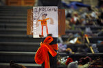 """A sign reading """"Indigenous Lives Matter"""" is taped to a lamp post in front of a memorial to the victims of Canada's residential school system made up of shoes, teddy bears, orange shirts and other tributes placed on the steps outside the legislature, in Victoria, Thursday, July 1, 2021.  (Chad Hipolito/The Canadian Press via AP)"""