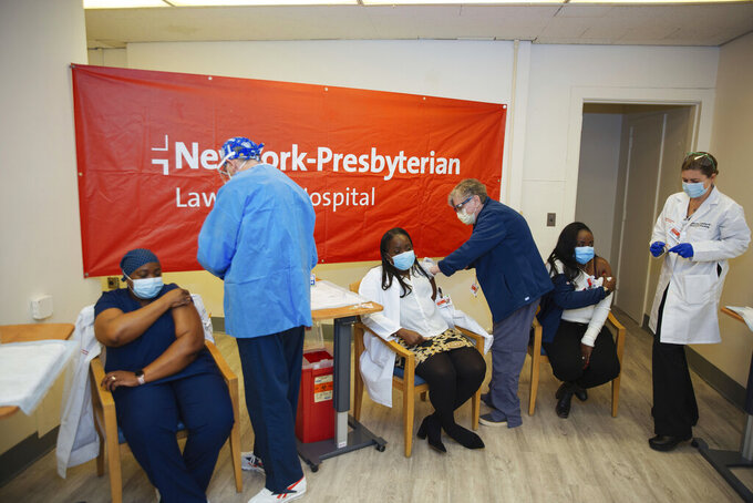 FILE - In this Friday, Jan. 8, 2021, file photo doctors inject sisters Claudia Scott-Mighty, left, Althea Scott-Bonaparte, who are patient care directors, and Christine Scott, an ICU nurse, with their second shot of the Pfizer vaccine at NewYork-Presbyterian Lawrence Hospital, in Bronxville, N.Y. The private New York-Presbyterian hospital system announced in June that it will require its 48,000 employees to be vaccinated unless they have a valid exemption. Workers in New York City-run hospitals and health clinics will have to get vaccinated or get tested weekly under a policy announced Wednesday, July 21, to battle a rise in COVID-19 cases fueled by the highly contagious delta variant. (AP Photo/Kevin Hagen, File)