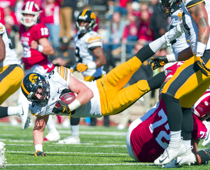 Iowa defensive back Jake Gervase (30) falls to the turf while being tackled by Indiana offensive players after intercepting a pass in the second half of an NCAA college football game Saturday, Oct. 13, 2018, in Bloomington, Ind. Iowa won 42-16. (AP Photo/Doug McSchooler)