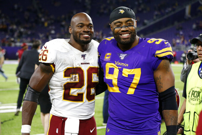 Washington Redskins running back Adrian Peterson (26) talks with Minnesota Vikings defensive end Everson Griffen after an NFL football game, Thursday, Oct. 24, 2019, in Minneapolis. The Vikings won 19-9. (AP Photo/Jim Mone)