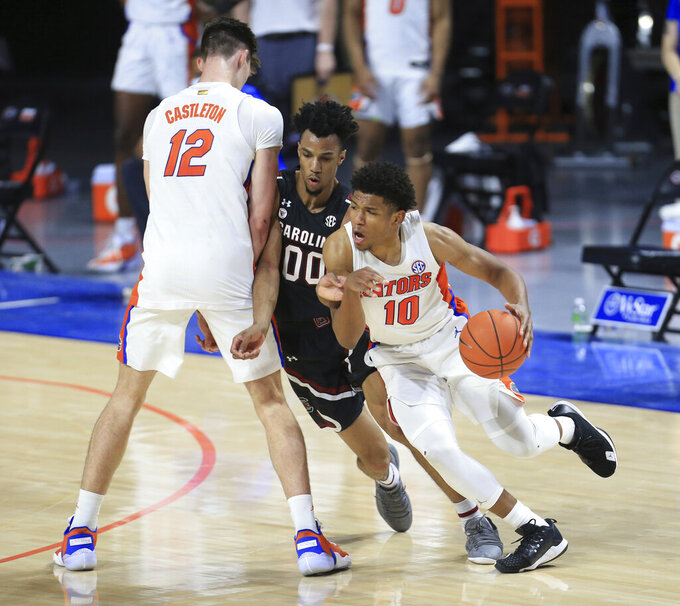 Florida guard Noah Locke (10) dribbles around South Carolina guard AJ Lawson (00) as forward Colin Castleton (12) sets a screen during the second half of an NCAA college basketball game Wednesday, Feb. 3, 2021, in Gainesville, Fla. (AP Photo/Matt Stamey)