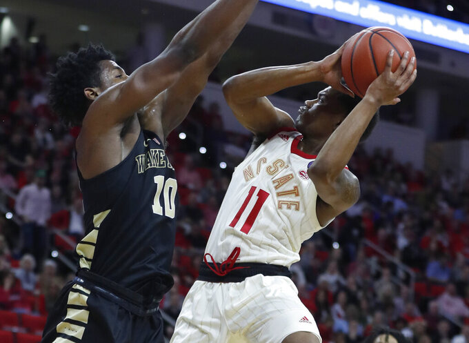 North Carolina State's Markell Johnson (11) shoots as Wake Forest's Jaylen Hoard (10) defends during the first half of an NCAA college basketball game, Sunday, Feb. 24, 2019 in Raleigh, N.C. (Ethan Hyman/The News & Observer via AP)