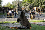 A piece of roofing, center, sticks out of the ground after landing in a yard across the street from a home that exploded at about 4:45 p.m. in the 4400 block of Cleveland Drive in Plano, Texas, Monday, July 19, 2021. (Stewart F. House/The Dallas Morning News via AP)