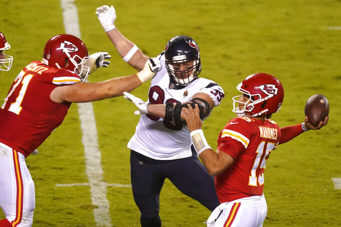 Kansas City Chiefs quarterback Patrick Mahomes (15) passes as he is pressured by Houston Texans defensive end J.J. Watt (99) in the first half of an NFL football game Thursday, Sept. 10, 2020, in Kansas City, Mo. (AP Photo/Charlie Riedel)