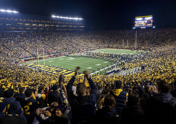 FILE - In this Oct. 13, 2018, file photo, fans cheer as the Michigan team takes the field at Michigan Stadium for an NCAA college football game against Wisconsin in Ann Arbor, Mich. While professional sports leagues can ponder plans to isolate their athletes from the coronavirus and have them play in unusual, even secluded places, college sports have no such option. Pro sports leagues can get creative with solutions to save their multibillion-dollar businesses. College sports will take a slower road back. (AP Photo/Tony Ding, File)