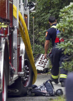 A firefighter stands near the wreckage of a single-engine plane behind a home on Minchin Drive, Saturday, Sept. 15, 2018, in Woburn, Mass. Officials said Dr. Michael Graver and Jodi Cohen were killed in the crash. The plane had departed from Republic Airport in Farmingdale, N.Y.,  and was en route to Laurence G. Hanscom Field in Bedford, Mass., about four miles from the crash site. (Nicolaus Czarnecki/The Boston Herald via AP)