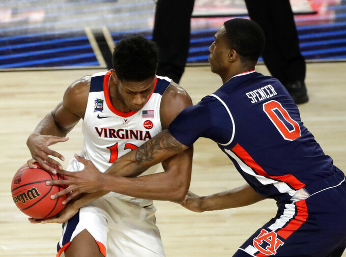 Auburn forward Horace Spencer tries to steal the ball from Virginia guard De'Andre Hunter, left, during the first half in the semifinals of the Final Four NCAA college basketball tournament, Saturday, April 6, 2019, in Minneapolis. (AP Photo/Matt York)