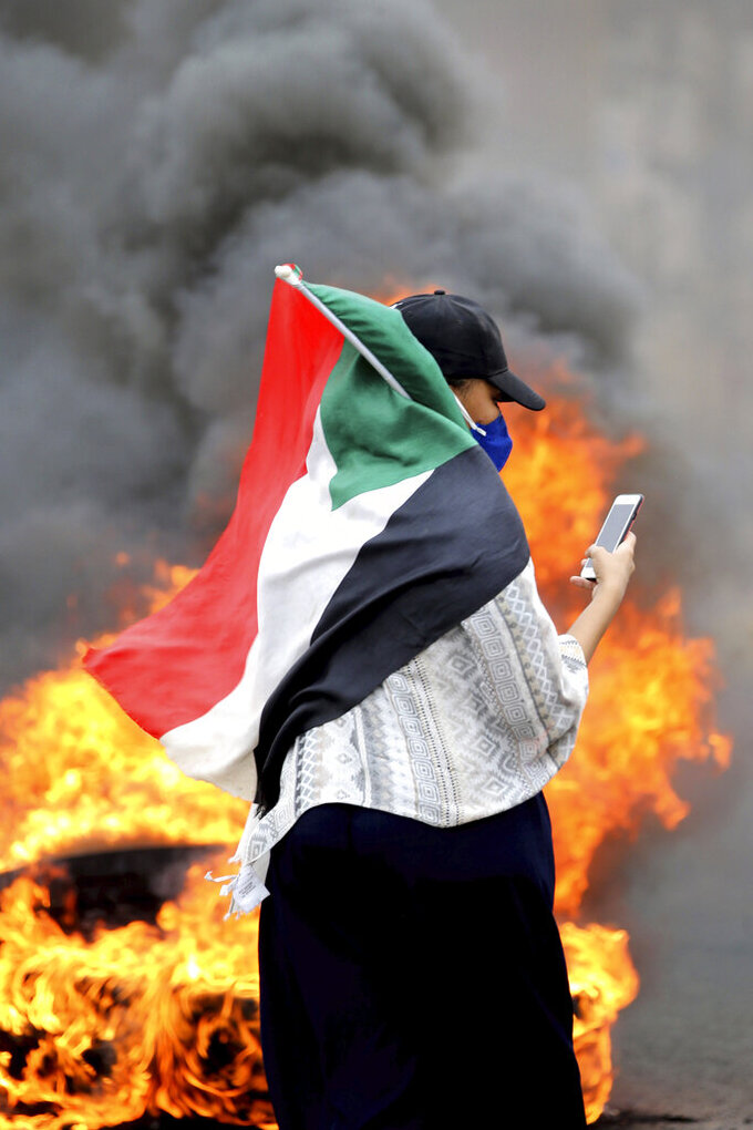 A Sudanese woman carries a national flag during a demonstration to commemorate the first anniversary of a deadly crackdown carried out by security forces on protesters during a sit-in outside the army headquarters, in Khartoum, Sudan, Saturday, May 23, 2020. (AP Photo/ Marwan Ali)