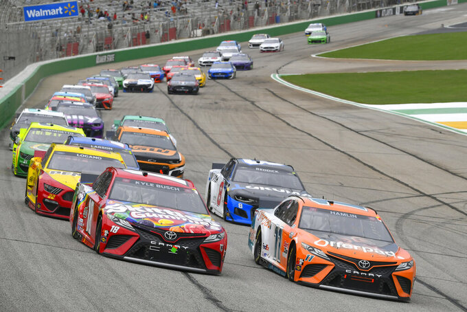 Kyle Busch, left, and Denny Hamlin (11) run in front after a release from the first caution during a NASCAR Cup Series auto race, Sunday, July, 11, 2021, in Hampton, Ga. (AP Photo/John Amis)