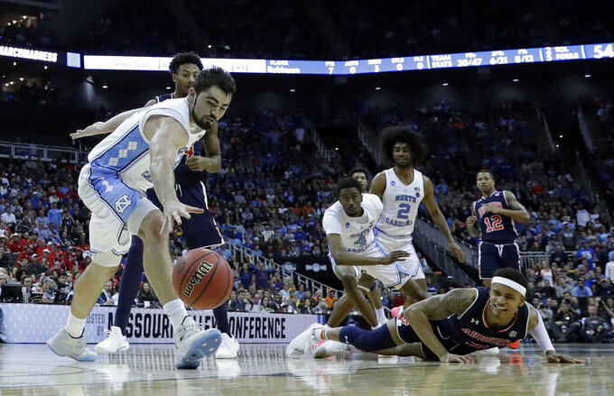 Auburn's Bryce Brown, bottom right, and North Carolina's Luke Maye, left, chase a loose ball during the second half of a men's NCAA tournament college basketball Midwest Regional semifinal game Friday, March 29, 2019, in Kansas City, Mo. (AP Photo/Charlie Riedel)