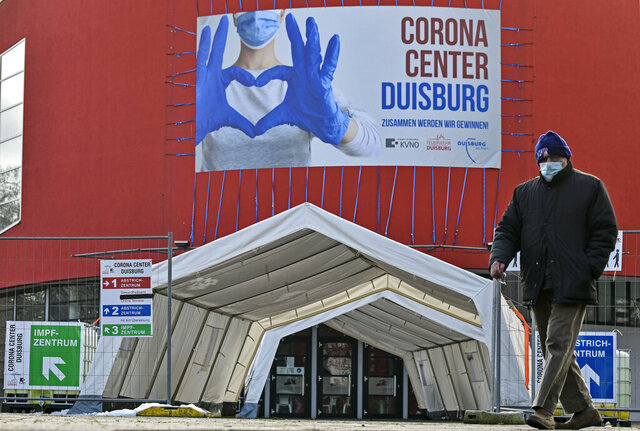 FILE - In this Monday, Jan. 25, 2021 file photo, a man wearing a face mask walks past the Corona Center in Duisburg, Germany. The former Musical theater has been turned into a COVID-19 test and vaccination center. Thousands of elderly Germans faced online error messages and jammed up hotlines Monday as technical problems marred the start of the coronavirus vaccine campaign for over-80s in the country's most populous state. (AP Photo/Martin Meissner, File)