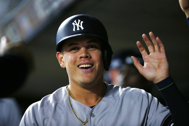 FILE - In this Monday, Oct. 7, 2019 file photo, New York Yankees' Gio Urshela celebrates in the dugout after scoring on a single by teammate Brett Gardner during the third inning in Game 3 of a baseball American League Division Series against the Minnesota Twins in Minneapolis. Yankees Gio Urshela had surgery Friday, Dec. 4, 2020 to remove a bone chip from his right elbow. (AP Photo/Bruce Kluckhohn, File)